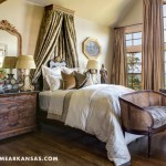 In the master suite, an antique corona is affixed to the bed's canopy, and a Louis Phillipe burl wood chest serves as a bedside table. At Home in Arkansas | November 2015