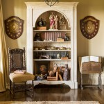 In a more intimate sitting room that adjoins the formal living room, a bookcase adorned with a diverse assortment of statues, books, and treasures also houses a collection of antique repousse boxes. Reproduction shields hand on either side of the the open-front bookcase. At Home in Arkansas | November 2015