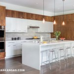 Clean lines, one of the Vurals' directives in the design, abound in the mix of wood-grain and white cabinetry in the kitchen. | Modern Thinking | At Home in Arkansas | Jan/Feb 2016
