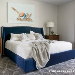 The master bedroom is one place in the home where color makes a grand statement in the form of a midnight blue velvet upholstered bedframe and complementary art. | Modern Thinking | At Home in Arkansas | Jan/Feb 2016