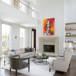 The architecture of the home allows the living room to take advantage of light from two stories. A bold, portrait-style painting over the fireplace adds a jolt of color to the neutral walls and furnishings. | Modern Thinking | At Home in Arkansas | Jan/Feb 2016