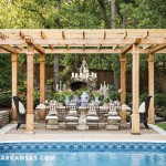 A wooden pergola frames the outdoor dining room—one of four main spaces nestled within the verdant landscape. The ten-foot concrete table comfortably accommodates ten people, making it ideal for hosting luncheons and dinner parties. Fresh-cut pink tulips and roses sit alongside small, potted plants for an alluring centerpiece, while an iron chandelier floats overhead to add to the European-inspired design. | At Home in Arkansas | March 2016