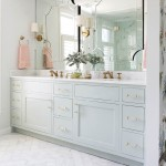 """The renovation of the master bath remedied an awkward layout by relocating the vanity, shower, tub, and water closet to one area and dedicating the rest of the space to becoming a fully functional closet. The double vanity is painted in Sherwin-Williams's """"Contented,"""" which is the same color seen on the walls throughout much of the home. 