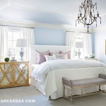 Custom white linen curtains, new bedding, and cheerful periwinkle walls brighten the master bedroom. The chandelier is by Visual Comfort and the painting is a sentimental piece by Tune's maternal great-grandmother, Estella Cynthia Nall Hankins. | A Perfect Pairing | At Home in Arkansas | May 2016
