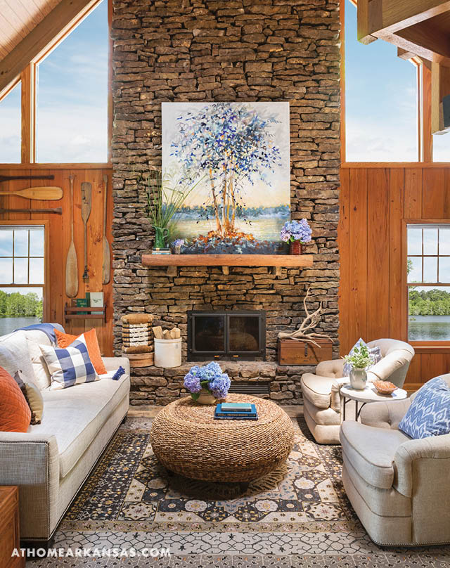 Brooks softened the cabin's rustic stone and wood by introducing a palette of blue and orange in the living room. The colors, seen in the art as well as the accessories, help to give the room a slightly more feminine feel while staying true to the natural setting. Castoff oars from the family's canoes are now wall art in the space. | Lakeside Legacy | At Home in Arkansas | July 2016