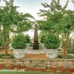 A quartet of crepe myrtles frames an obelisk fountain and concrete planters that are filled with boxwoods. | A Gracious Planting | At Home in Arkansas | July 2016