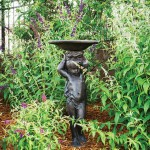 An iron figural birdbath was a birthday gift from his brother and sister-in-law that Robinson intends to fill with stones and shallow water to use as a butterfly bath for the numerous winged visitors to his garden. | A Gracious Planting | At Home in Arkansas | July 2016