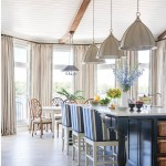 The five-foot-long kitchen island and nearby wet bar wear a custom navy stain. The barstools are by Ballard Designs; Brun chose to upholster them in a stripe fabric by Sunbrella for its durability. Large-scale pendant lights by Currey & Co. make a dramatic statement, while the floor is ceramic tile fabricated to resemble an understated limestone. | Rooms With A View | At Home in Arkansas | July 2016