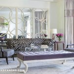 In the formal living room, a large rug connects two seating areas. Seating is by Suzanne Kasler for Hickory Chair and Barbara Barry for Henredon. Designer Kevin Walsh of Bear Hill Interiors had the loveseat recovered in a bold animal print, and repurposed the homeowner's mirror. Lavender silk draperies have an embroidered trim, and cabinets flanking the fireplace are outfitted with new doors and ring-pull hardware. | Home at Last | At Home in Arkansas | August 2016