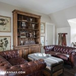 """Upstairs, the design for the common family room was laid out to include the dormer areas as a part of the space, rather than separate nooks. Groppetti notes that this """"makes the room [appear] bigger and more functional instead of treating the dormers as separate features."""" A pair of Chesterfield sofas lends a masculine feel to the room and summons a cozy afternoon nap, while a large wooden cabinet piece provides display space and storage.  