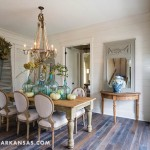 """""""The entire floor plan moves through the dining room,"""" Groppetti notes. """"It is the true hub of the home. We liked this idea because too often the dining room is off to one side and only used for certain occasions. With this plan, everything flows through this space."""" Again, wood flooring and farmhouse-style furnishings provide continuity throughout the spaces. 