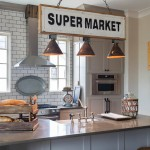 In the kitchen, Franks chose timeless Shaker cabinetry and paired it with classic white subway tile on an extended backsplash area. The light fixture is a custom creation made from Park Hill metal signs and vintage tin chicken feeder parts.  | Best in Show | At Home in Arkansas | November 2016