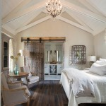 In the master bedroom, Franks employed vaulted cathedral ceilings for a spacious sense of grandeur. The shiplap application keeps the design grounded in simplicity, while a crystal chandelier adds a hint of fancifulness to the room. A sliding barn door, made of refurbished boxcar wood that Franks found at 2Brothers Reclaimed & Repurposed Inventory Sales in Menifee, conceals the entrance to the master bath. | Best in Show | At Home in Arkansas | November 2016