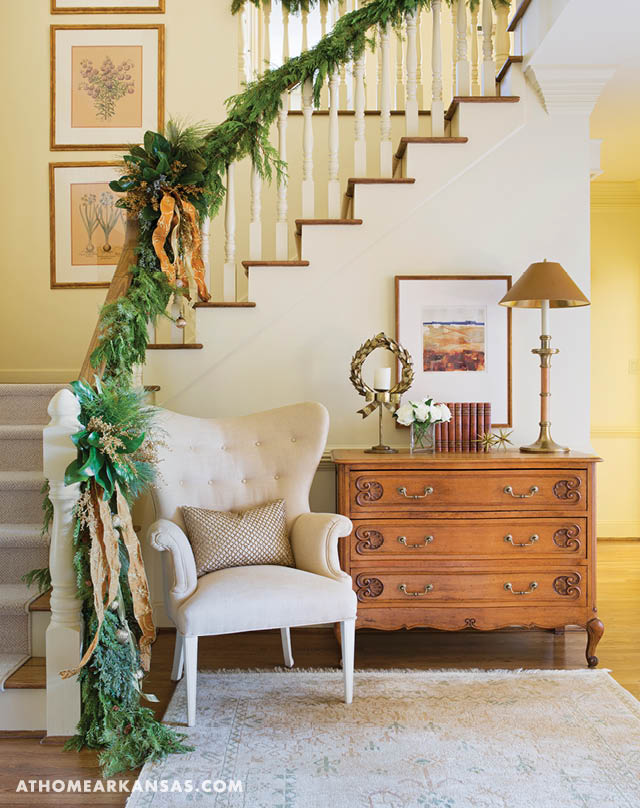 An antique chest and shapely wing chair set a relaxed, but refined, tone in the entry hall. The stair banister is wrapped in a mixed-green garland accented with magnolia leaves, gold ribbon, berries, and baubles. | Full House | At Home in Arkansas | December 2016