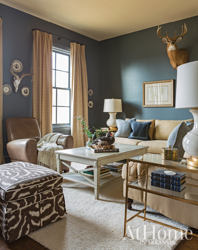 Deeper hues of the blue, green, and neutral-toned palette abound in Jill's brother-in-law George's study, which is also a favorite napping place for one of the couple's sons. Enveloped in a deep blue gray, the room is arguably one of the coziest in the house. An equal mix of new finds and pieces the couple already owned comprise the room's makeup. The ottoman was a piece that struggled to find a home following the move; however, Jill gave it new life with a spirited Ralph Lauren animal-print fabric and positioned it here where it provides extra seating and echoes the taxidermy pieces.