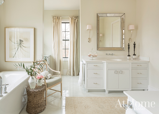 To create visual interest in this master bathroom, Jill paired contemporary elements—such as the wall-mount faucet and geometric hardware—with timeless elegant selections, including the freestanding soaker tub, a soft neutral-based palette, and the addition of a classic rug.