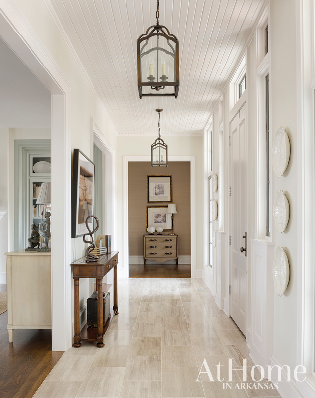"As with many entry spaces, the foyer sets the tone for this house: comfortable and classic yet interesting. Designer Jill Lawrence notes that a veined travertine tile is a ""nice little showstopper"" underfoot, while iron lanterns hang from the beadboard ceiling and echo the black seen on the interior mullions of the windows."