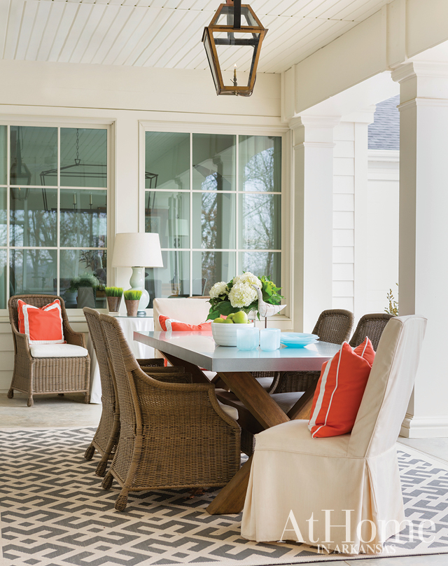 """The casual yet sophisticated feel of the home extends beyond its walls onto a covered patio, located just off the living room. """"When you have a lot of windows facing your outdoor spaces, the interior and exterior need to blend and have like components because they all mesh together as one big space,"""" Jill says. """"I always try to make sure that my outdoor accents go with the interior. They don't have to completely match but you need to be able to look out there and recognize there's a flow."""""""