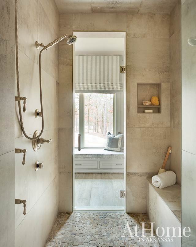 A walk-through shower leads from the vanity through to a window seat on the opposite side. Uncovered windows allow natural light to spill into the shower, though a shade can be lowered when desired.