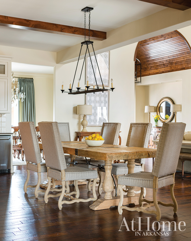 Acacia wood floors run throughout the majority of the home, providing a continuous base from room to room. Their dark hues complement the lighter pinewood table that sits between the kitchen island and the living room.