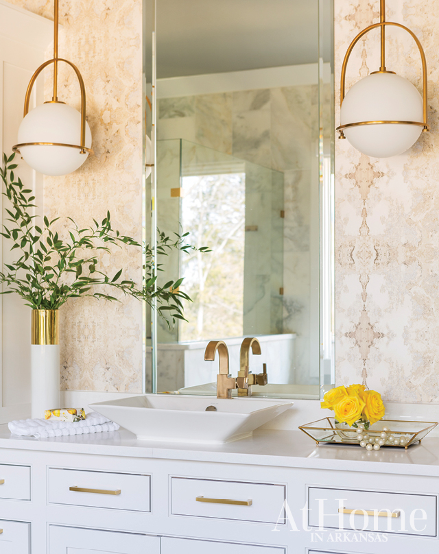 Floor-to-ceiling marble near the shower gives the spacious master bathroom the feel of a spa. An inkblot-inspired wallpaper by Candace Olson for York, a modern sink, and suspended globe lights make the room contemporary yet timeless.