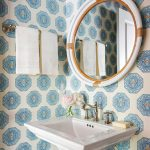 "The walls of this cheery powder bath are covered in Quadrille's ""Medallion"" wallpaper. A Serena & Lily mirror echoes the home's slightly coastal vibe."